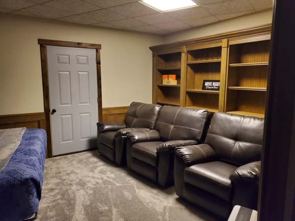 Bedroom with king bed, book shelving and 3 recliners