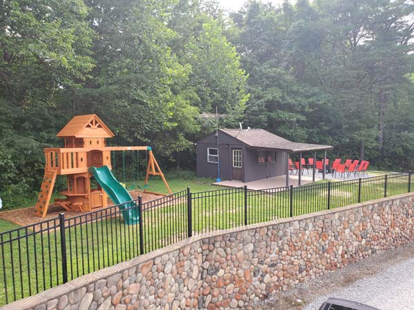 Outside showing children's play house, love shack and fire pit with ample seating.