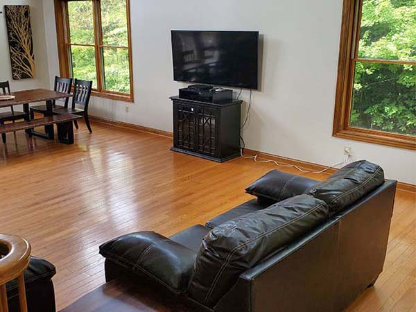 Loveseat in front living room with flat screen tv and large windows.
