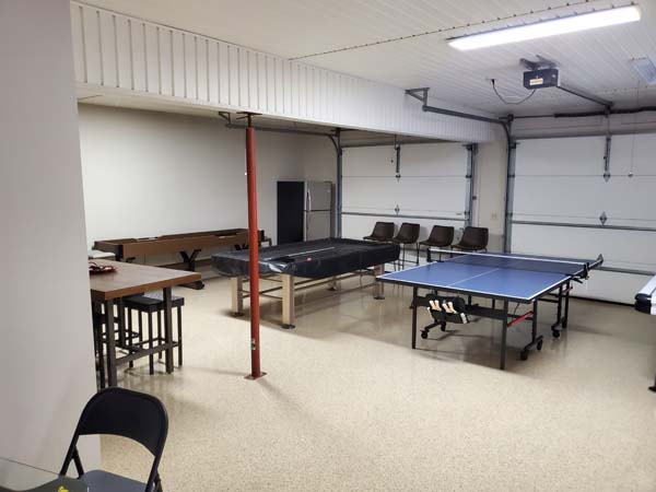 Downstairs rec room with pool table, ping pong table, shuffle board table, refrigerator, and ample seating