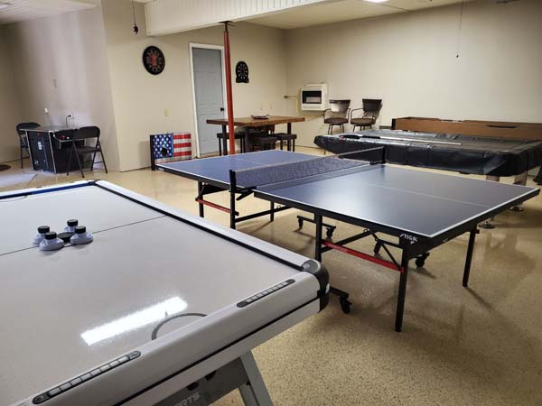 Downstairs rec room with air hocking table, ping pong, arcade game machine.