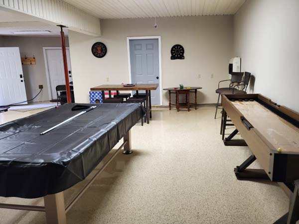 corner of rec room game tables near shuffle board table.
