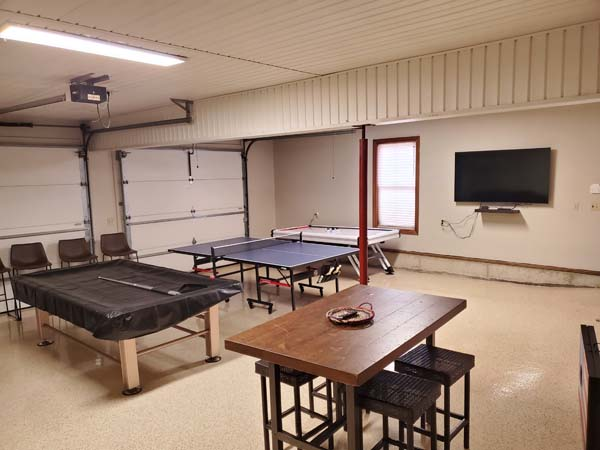 opposite end of rec room game tables and flat screen wall mounted tv