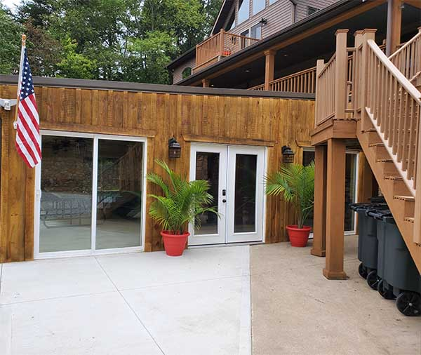 Exterior front entrance to pool house with potted palm trees